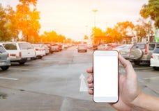 Intelligentes Telefon, das leeren Bildschirm in der Mannhand mit UnschärfeParkplatz zeigt Stockfotografie