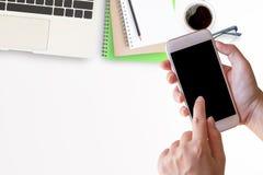 Intelligentes Telefon in der weiblichen Hand mit Schreibtisch mit Laptop stockfoto