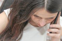 Intelligentes Telefon des attraktiven Geschäftsfrau-Gebrauches und Sitzen an ihrem wor Stockfoto