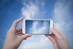 Intelligentes Telefon des Frauengebrauches machen ein Foto des blauen Himmels und der schönen Wolke Stockbild