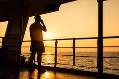 Intelligentes Telefon des Gebrauches des jungen Mannes auf dem Schiff Stockfoto