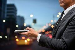 Intelligentes Telefon des Geschäftsmann-Griffs mit Stadtlicht im Hintergrund Stockfotos