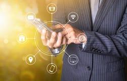 Intelligentes Telefon des Geschäftsmanngebrauches mit multichanel on-line--communicatio Lizenzfreie Stockfotografie