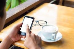 Intelligentes Telefon des Manngebrauches in der Kaffeestube Lizenzfreie Stockfotografie