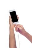 Intelligentes Telefon mit dem leeren Bildschirm und Ladegerät in der Hand lokalisiert Stockfotografie