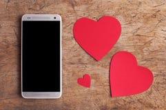 Intelligentes Telefon mit leerem Bildschirm und rote Papierherzen auf altem Holztisch Stockbild