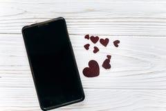 Intelligentes Telefon mit leerem Schirm und flache Lage der Herzen auf weißem backg Lizenzfreie Stockbilder