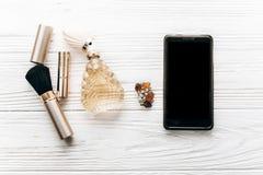 Intelligentes Telefon mit leerem Schirm- und Luxusschmuckparfüm bilden Lizenzfreie Stockfotografie