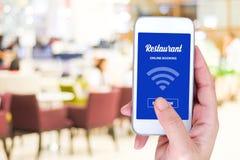 Intelligentes Telefon mit on-line-Anmeldung auf Schirm über Unschärferestaurant b lizenzfreies stockfoto