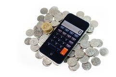 Intelligentes Telefon mit Münzen auf Isolat Stockfotos
