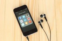 Intelligentes Telefon mit Social Media-Logos auf seinem Schirm und Kopfhörern Stockbilder