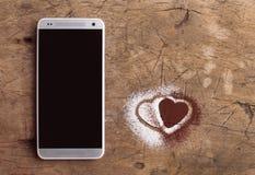 Intelligentes Telefon und Herzen des Zuckers und des Kakaos Stockfoto