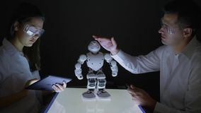 Intelligenza artificiale, ingegneri tecnici che lavorano collaborazione sul progetto per costruire robot in officina stock footage