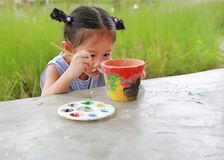 Intend Asian kid girl paint on earthenware dish royalty free stock photography