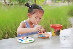 Intend Asian kid girl paint on earthenware dish.  stock photos