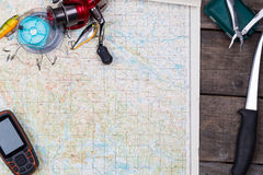Intend with fishing tackles and navigator on map Stock Photography