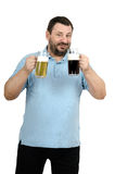 Jolly bartender offering beers on the house. Jolly bearded bartender in polo shirt offering two beers on the house Royalty Free Stock Photography