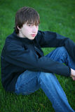 Intense. Handsome teen guy model seated in grass Stock Images