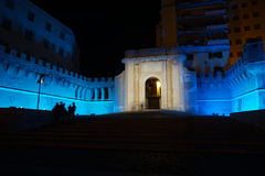 An intense blue light illuminates Porta Livorno in the night. Civitavecchia Rome Italy A special light game of intense blue color that beautifies Vanvitelli`s Royalty Free Stock Photo