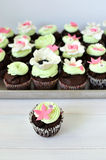Intense chocolate cupcakes. Topped with white chocolate mascarpone frosting and decorated with fondant flowers Royalty Free Stock Photography