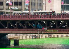 Intense crowds of party-goers gather on Michigan Avenue over a dyed green Chicago River. On St. Patrick`s Day stock photo