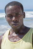 Intense determination. Closeup of young lean sweaty African American male athlete with expression of intense determination at beach Royalty Free Stock Image
