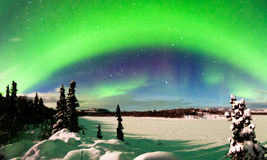 Intense display of Northern Lights Aurora borealis. Spectacular display of intense Northern Lights or Aurora borealis or polar lights forming green arc over Stock Images