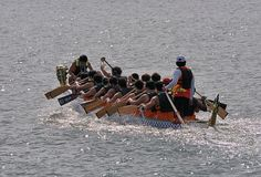 Intense Dragon Boat Paddling. Dragon boat festival or races are often held in Asia to help nurture cultural awareness and empower business community in economic Stock Image