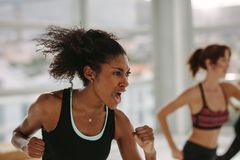 Intense fitness training in gym. Woman working out with full strength in class at health club stock photo