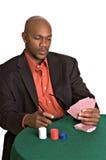 Intense gambler. Intense African-American man playing poker stock photography