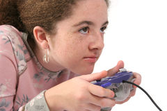 Intense Gamer. A teenaged girl holding a game controller, with an intense look of concentration.  Isolated Stock Photography