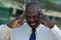 Intense headache. Businessman under a ton of stress Stock Image