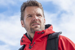 Intense hiker. Closeup of determined bearded Caucasian man hiking with intense strenuous expression wearing red jacket and sky in background Royalty Free Stock Photos