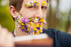Intense look of a flower covered hipster reading Royalty Free Stock Photography