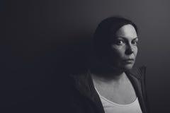 Intense low key portrait of pensive sad woman Stock Images