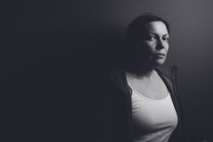 Intense low key portrait of pensive sad woman. Leaning on gray room wall, low contrast monochromatic image royalty free stock photos