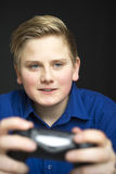Intense male youth in blue with game controller. Single intense male youth in blue shirt with grin and blond hair holding a dual joystick video game controller Royalty Free Stock Photos