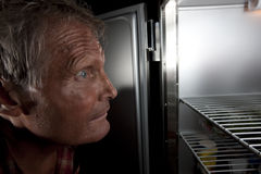 Intense Man Staring Into Refrigerator. Close-up profile of a middle-aged man staring intensely into a refrigerator that is mostly empty. Horizontal format Royalty Free Stock Images