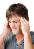 Intense migraine. Young man has headache and shows pain on his face Stock Photography