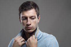 Intense moody portrait of young stubble man holding collar looking behind Stock Images