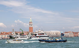Intense Nautical Traffic in Venice. Venice, Italy- July 28,2011: Various boats and ships carring people and products towsailing in the waters of Grand Canal in Royalty Free Stock Photos