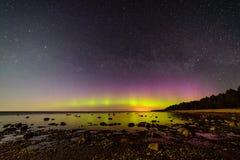 Intense northern lights (Aurora borealis) over Baltic sea. Rocky beach stock photos