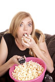 Intense popcorn. A woman sitting on a bean bag while she is enjoying her popcorn while she is watching TV with intense eyes Royalty Free Stock Photo