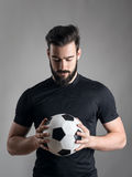 Intense portrait of football player holding and looking at the ball focused over gray studio background Stock Photo