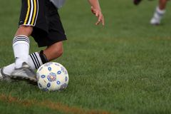 Intense Soccer Kick. Soccer girl kicking ball hard Royalty Free Stock Photography