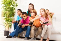 Intense video game with friends. Group portrait of diversity looking children boys and girls, friends, playing videogame sitting on the couch in living room with Royalty Free Stock Photo