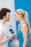 Intense young couple working out with dumbbells. Standing face to face exercising together and egging each other on to greater achievements Royalty Free Stock Images