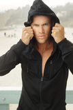 Intense young man. In black hooded workout clothing outdoors Stock Images