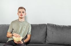 Intensed Boy Watches Horror Film. Intensed fair hair boy watches a horror film, eating popcorn on the comfortable grey sofa, scared emotion Royalty Free Stock Photo