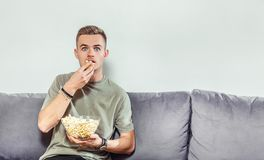 Intensed Boy Watches Horror Film. Intensed fair hair boy watches a horror film, eating popcorn on the comfortable grey sofa, scared emotion Royalty Free Stock Image